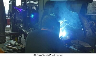 Welder in action, repairing an old car.