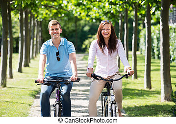 Smiling Couple Riding On Bicycles