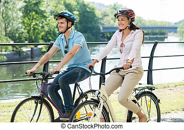 Couple On Bicycles Ride In The Park