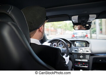 Male Chauffeur In Car - Rear View Of A Male Chauffeur...