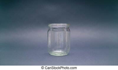 Woman Puts American Dollar 100 into a Glass Jar for Storage....
