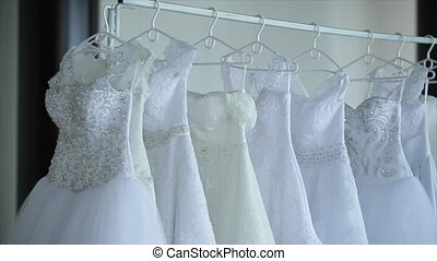 wedding dresses hanging on racks.