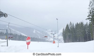 Ski lift in the fog, with skiers