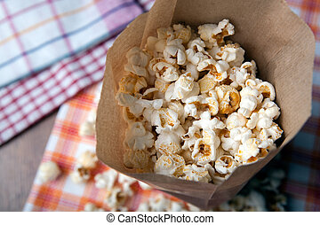 salted popcorn in a paper bag close up - fresh salted...