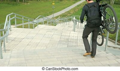 A young man carries a bicycle through the long stairs. Against the background of green field. Clouds changing light stairs
