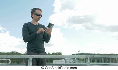 Outdoor portrait of modern young man with digital tablet. A man with glasses on the bridge. Behind the blue sky