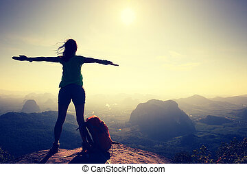 silhouette of free cheering woman hiker open arms at...
