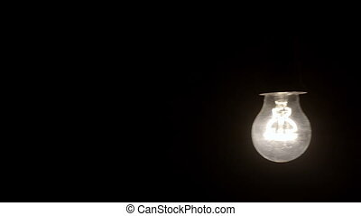 Glowing hanging light bulb dangle on a wire LOOP