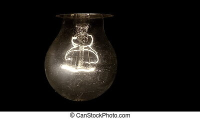 Glowing hanging light bulb dangle on a wire