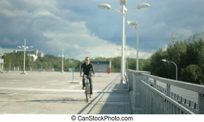 Male cyclist riding down the street and stopped because of a...