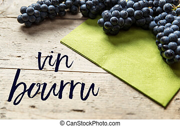 Blue grapes on wooden table, french text, concept...