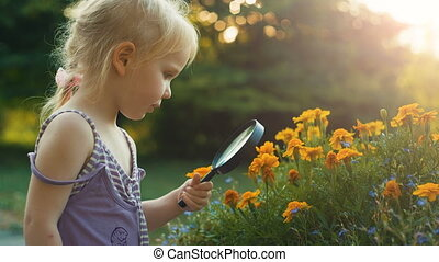 Girl with magnifying glass exploring flowers - Little...