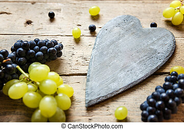 White and blue grapes and a wooden heart with copyspace,...