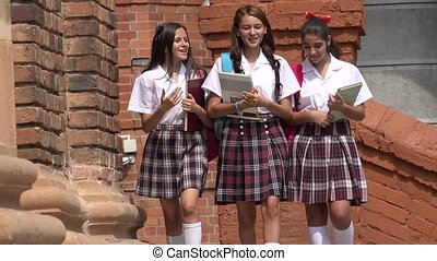 Teen Girls Carrying Books