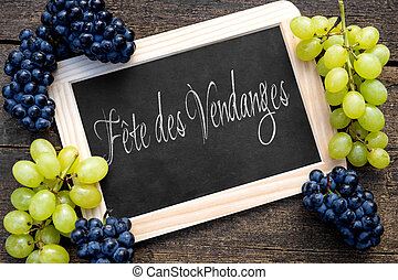 blue and white grapes with a slate on wooden table - white...