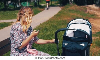 Mother sway baby carriage sit on bench and using smartphone....