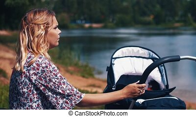 Mother sway baby carriage sitting on bench at lake. Summer...