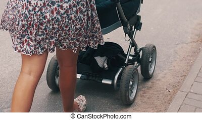 Back side mother walking with baby carriage on road. Summer day. Motherhood.