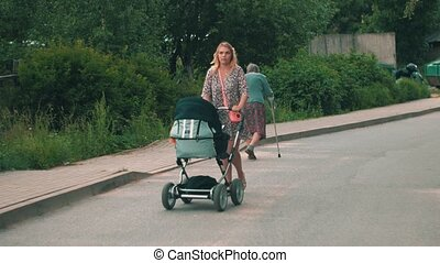 Mother walking with baby carriage in green park. Summer day....
