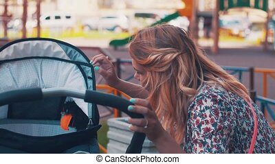 Mother sway baby carriage on children playground Summer day...
