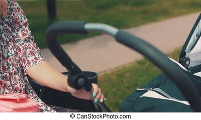 Mother sway baby carriage and speaking on phone in park...