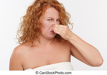 Mature woman holding her nose - Bad smell makes this woman...