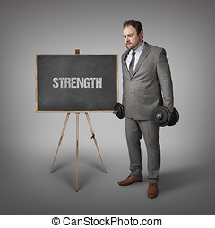 Strength text on blackboard with businesssman holding...