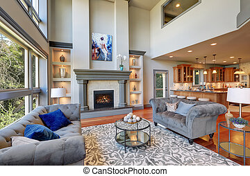 Grey interior of high vaulted ceiling family room. - Grey...