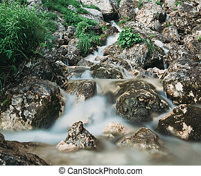 Mountain brook flowing among stones
