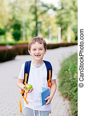Happy little 7 years old boy at his first day at school ....