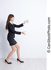 Business woman pushing with white wall background, asian
