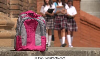 Female Students Walking Towards Backpack