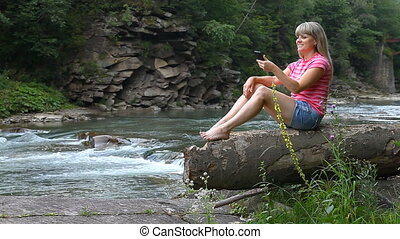 A young girl sits at the river and photographing themselves on a smartphone.