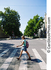 young woman with backpack and coffee crossing the street