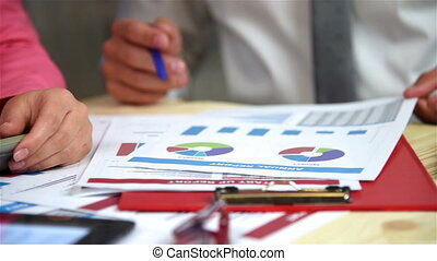 Business Employees Examines Annual Reports On The Table....