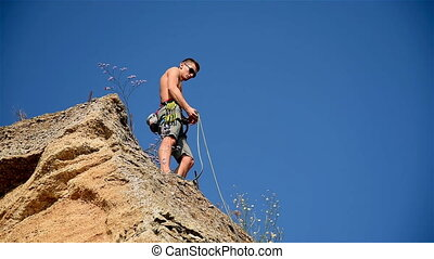 Climber Standing On Top Of Cliff And Wound Rope