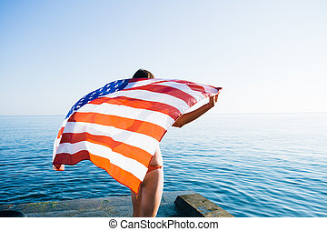 Back view of female with American flag against sea - Rear...
