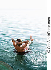 Back view of relaxing woman floating on inflatable ring -...