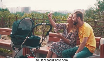 Mother and father sway baby carriage on bench Take selfie...