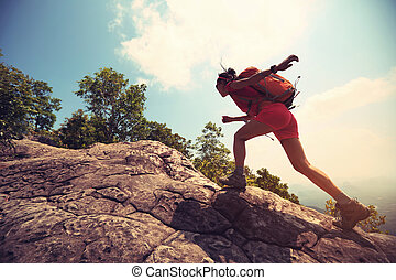 young asian woman hiker climbing rock on mountain peak cliff