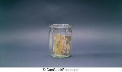 Woman Puts Canada Dollar 100 into a Glass Jar for Storage....