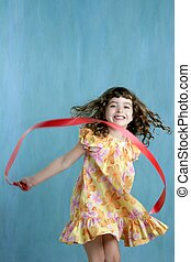 little girl red ribbon tape dancing over green - action...
