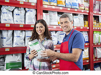 Confident Salesman Assisting Customer In Buying Pet Food -...
