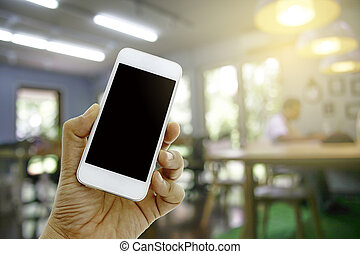 hand hold smart phone on blurred man with laptop - hand hold...