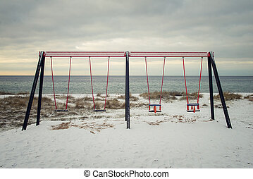 swings - empty swings on the beach in winter