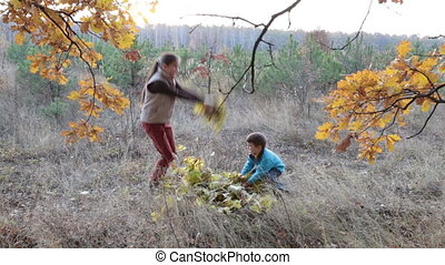 Two kids throwing autumn leaves in the forest