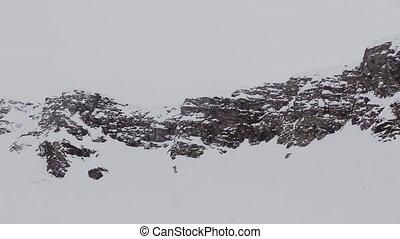 Panoramic view of snowy mountains peaks. Grey weather. Nature. Landscape