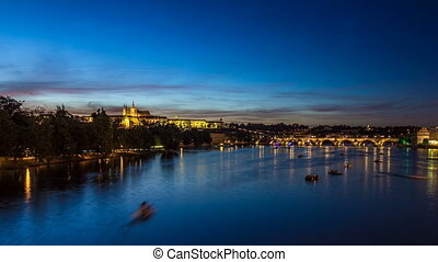 View of the city Prague in Czech Republic with colorful paddle boats day to night timelapse on the Vltava river with beautiful sky