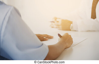 close up of doctor taking notes at hospital