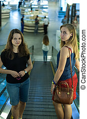 Two girls on escalator